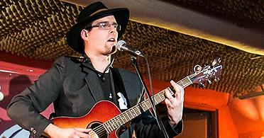 młody mężczyzna w okularach gra na gitarze