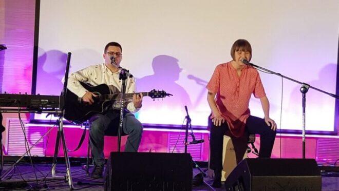 młody gitarzysta i młda wokalistka na scenie. Wokalistka siedzi na cajonie