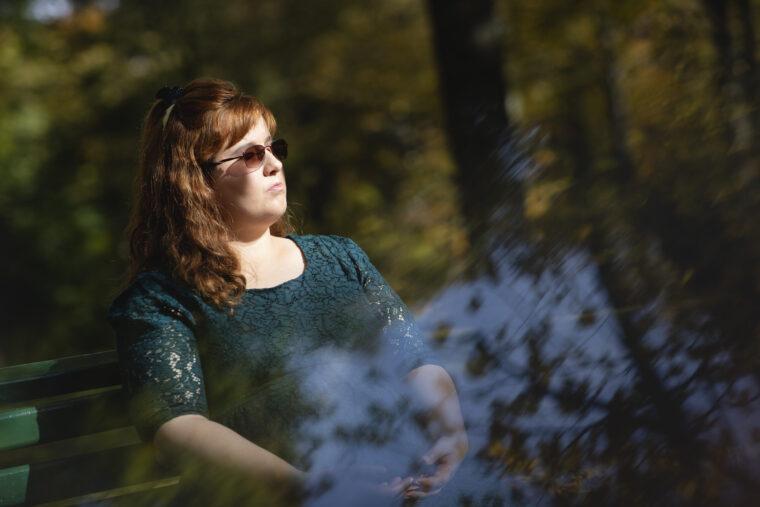 młoda kobieta w okulrach siedzi na łąwce, patrzy w dal