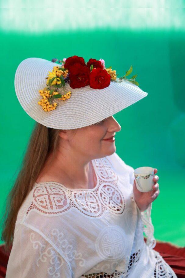 młoda dłuygowłosa kobieta w wielkim kapeluszu