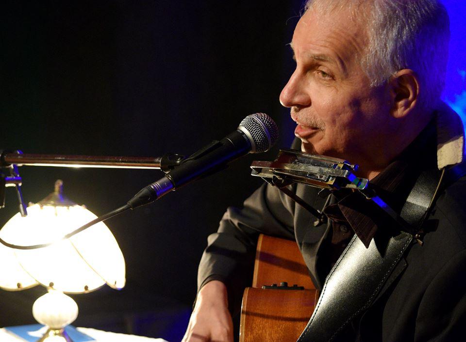 siwy mężczyzna gra na gitarze