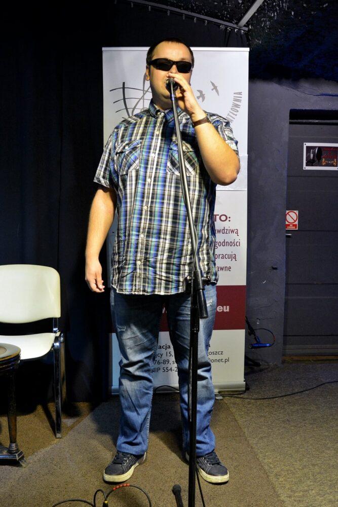 młody mężczyzna w kraciastej koszulu śpiewa